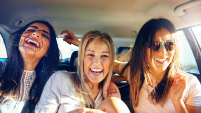 photo of authentic women laughing in a car