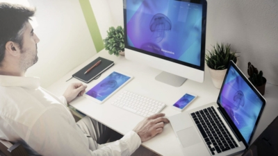 photo of man using two computers to combine websites