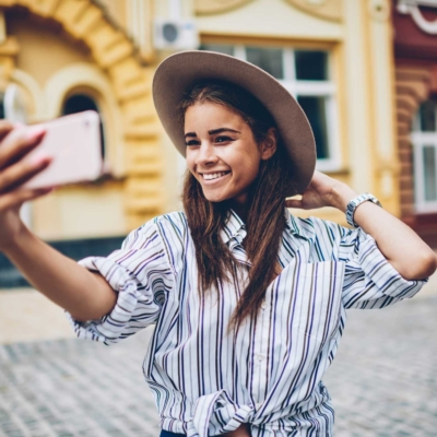 photo of young woman taking a selfie in a foreign city
