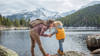 photo of a mother and son hikers in front a lake with mountains and evergreen trees in the background