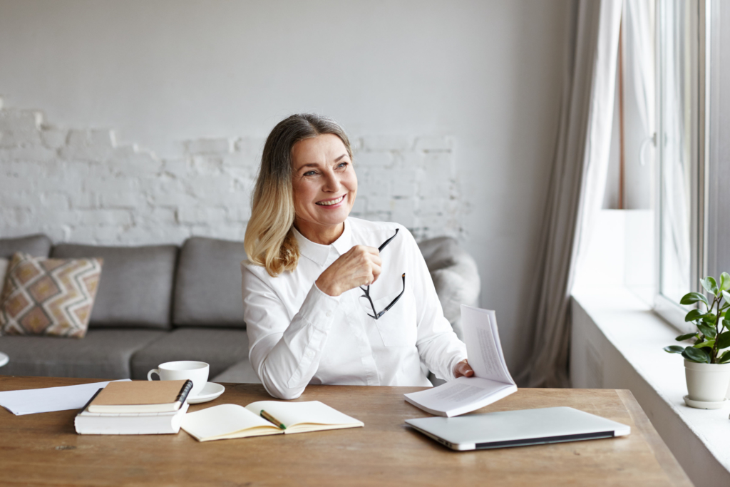 photo of woman author sitting at desk reading with books & laptop