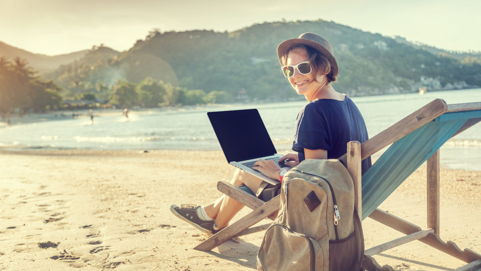 photo of blogger working on beach with laptop