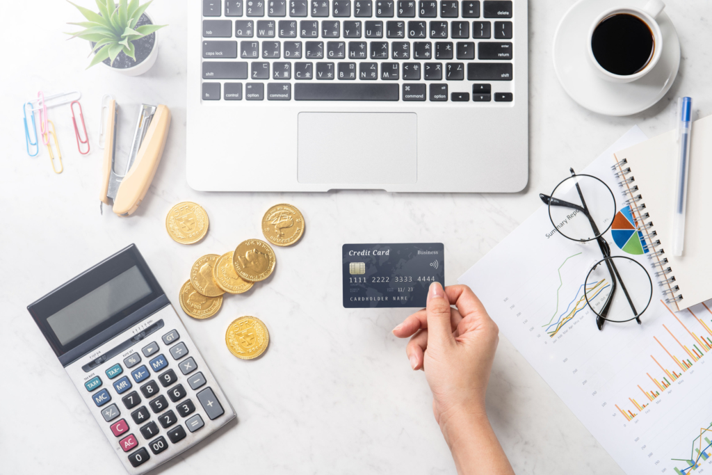 photo of hand holding credit card next to coins and laptop representing ecommerce website