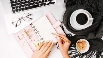 photo of feminine blogger writing in planner at her desk