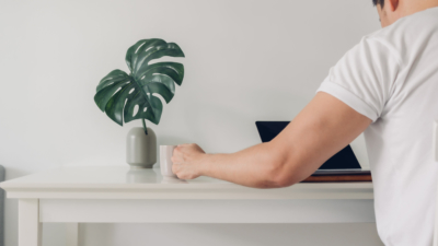 minimalist photo of a person sitting at a white desk with green plant