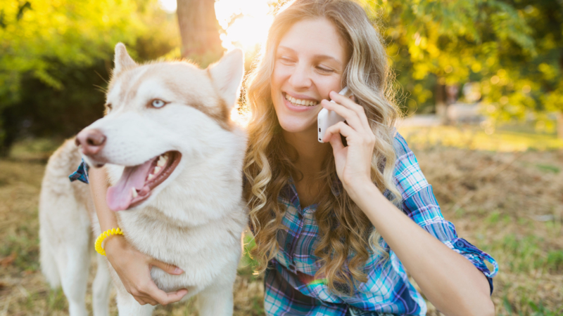 photo of woman and her dog at park while she talks on phone