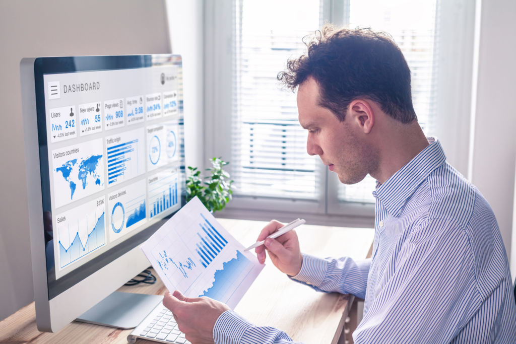 photo of man studying analytics at his desk, computer with charts on screen