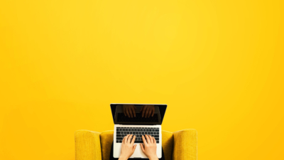 photo of seated person on laptop with yellow minimalist background