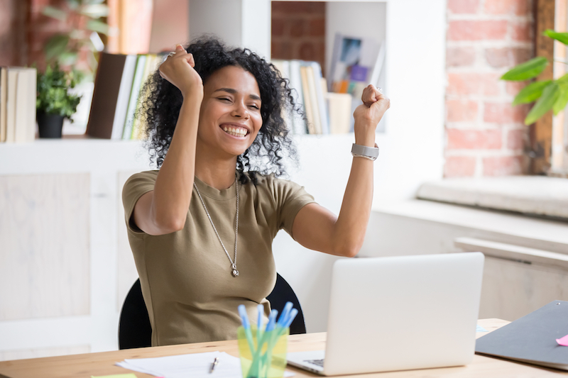 Photo of woman with arms raised in excitement